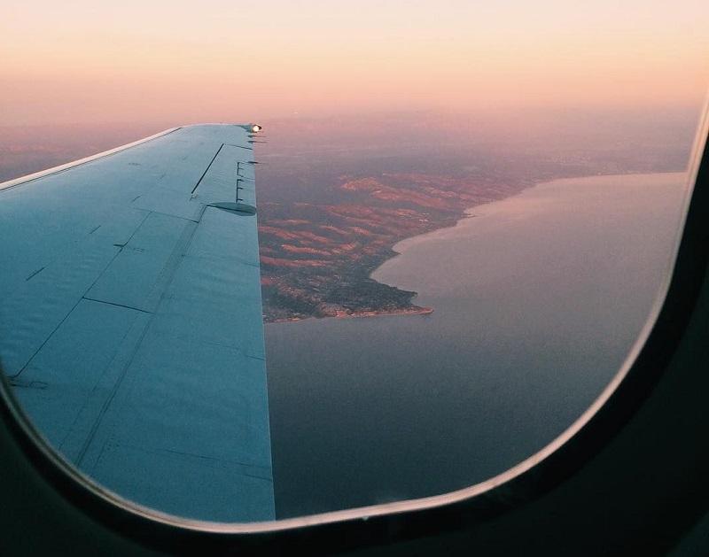 Janela de avião com vista paradisíaca